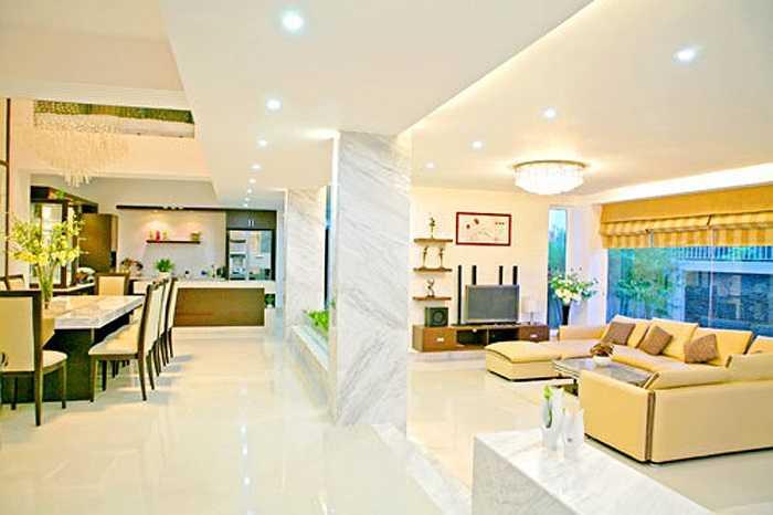 Phòng khách và phòng ăn được ngăn cách bởi một bức tưởng nhưng có nhiều khoảng trống tạo không gian thoáng đãng.