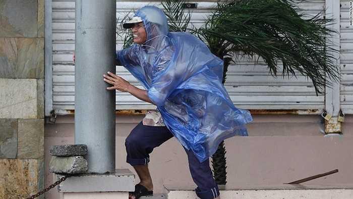 Người đàn ông bám trụ vào cột trong gió bão ở Legazpi sáng 7/12
