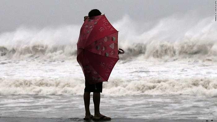 Một người dân liều lĩnh đứng ở mép nước trong bão