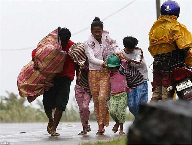 Một gia đình ở  Marabot, đảo Samar di chuyển khỏi khu vực nguy hiểm