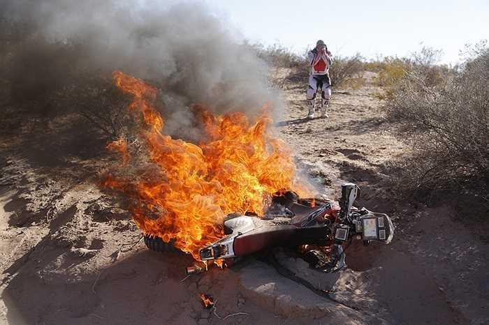 Tay lái Paulo Goncalves của đội Honda bất lực trước chiếc xe đang bốc cháy khi tham gia cuộc đua đường trường Dakar tại Argentina ngày 9/1/2014