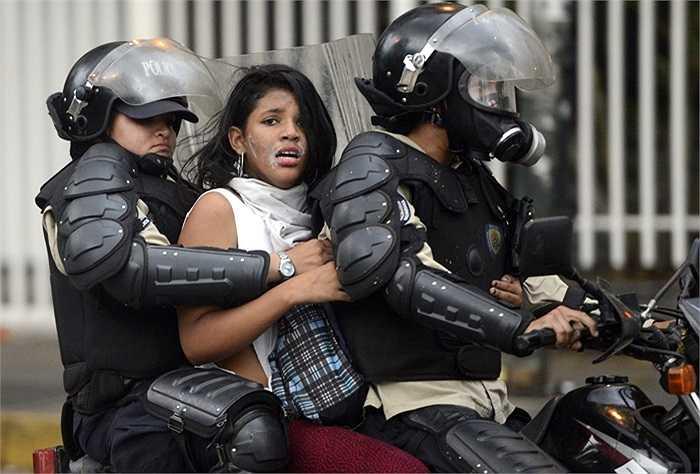 Nữ biểu tình bị cảnh sát khống chế tại Venezuela ngày 13/3/2014