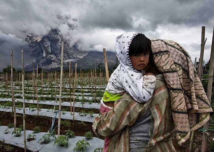 Bé gái được mẹ bế khi núi lửa phun trào trên đảo Sumatra, Indonesia ngày 4/1/2014