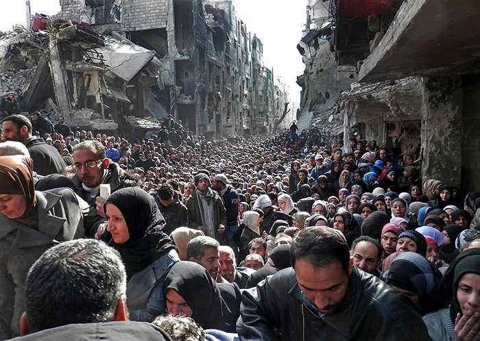 Người dân tụ tập nhận hàng viện trợ, thức ăn tại Damascus, Syria vào ngày 31/1/2014