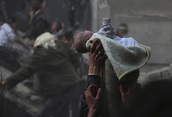 Người đàn ông giơ cao em bé sống sót trong đống đổ nát của cuộc không kích tại Damascus, Syria ngày 7/1/2014