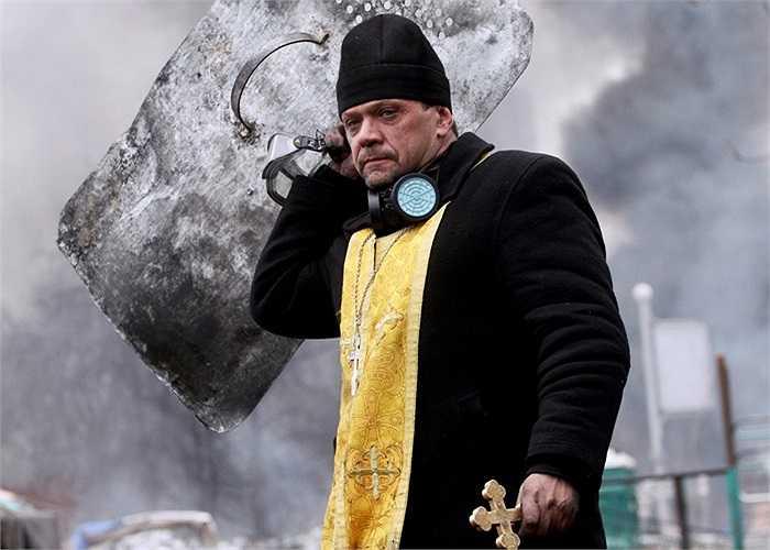 Thầy tu cầm thánh giá và khiên trong cuộc biểu tình ở trung tâm Kiev, Ukraine ngày 20/2/2014
