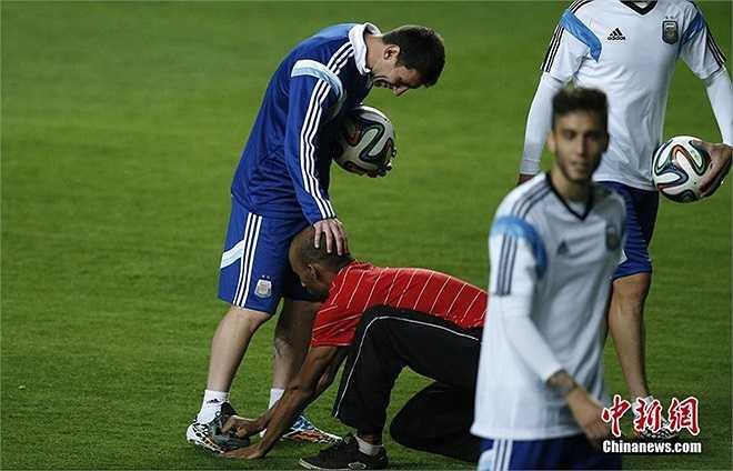 Một CĐV thoát khỏi sự ngăn cản của nhân viên an ninh khi vào sân để thể hiện sự hâm mộ với Messi. Anh lau giày cho Leo trong khi ĐT Argentina khởi động trước trận đấu bảng F gặp Iran tại World Cup 2014.