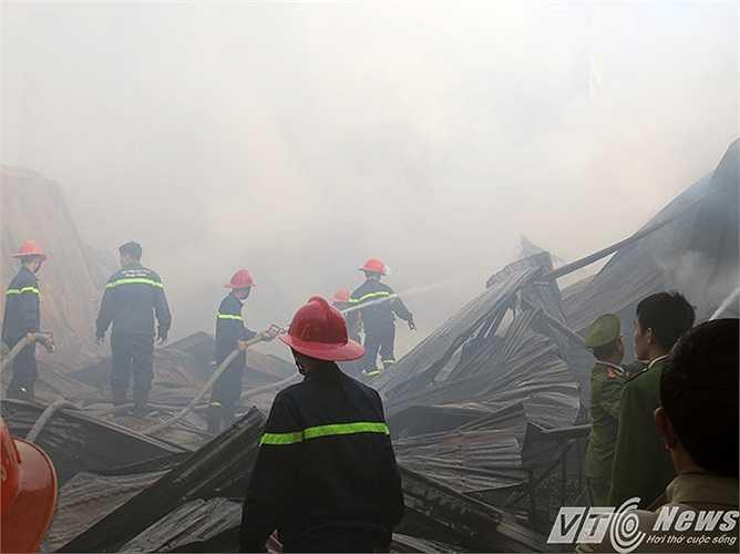 Lực lượng PCCC tiếp cận hiện trường bên trong nhà xưởng, dùng vòi rồng dập lửa, chống bùng phát trở lại.
