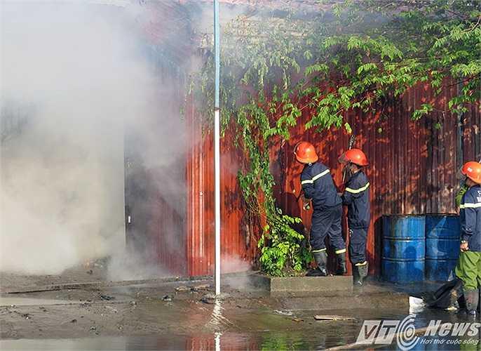 Các chiến sỹ Cảnh sát PCCC phá tường bao nhà kho để phun nước vào dập lửa