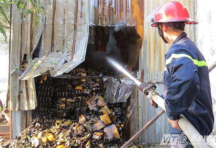 Lược lượng PCCC phải phá cửa kho để phun nước dập lửa, tránh lan rộng.