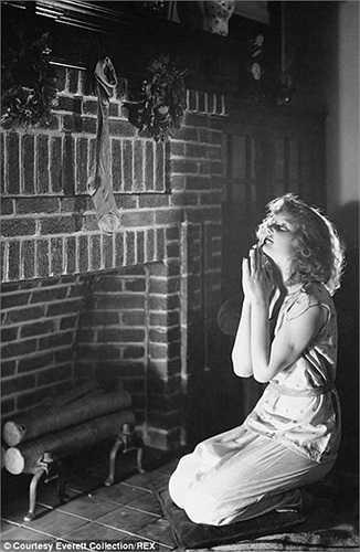 Người phụ nữ ngồi cầu nguyện bên lò sưởi Giáng sinh