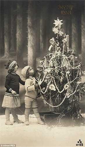 Hai đứa trẻ Pháp bên cạnh cây thông Noel