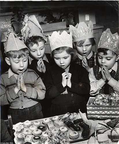 Những đứa trẻ cầu nguyện bên chiếc bánh mừng Giáng sinh