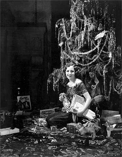 Người phụ nữ ngồi bên những món quà dưới cây thông Noel
