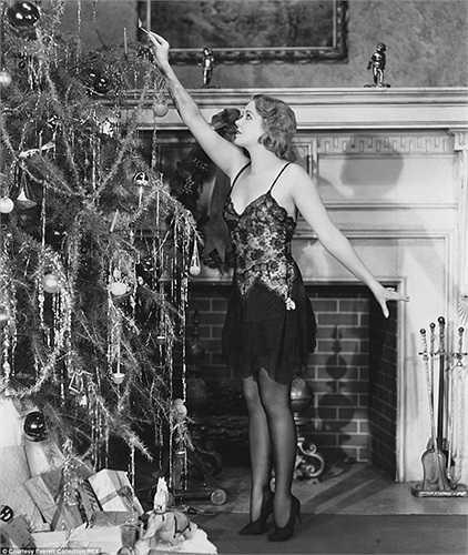 Cô gái trẻ đẹp làm dáng bên cây thông Noel trong bức ảnh chụp năm 1910