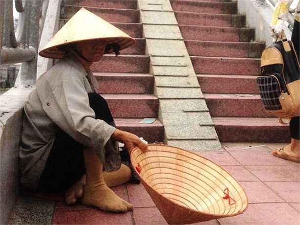 Một người già đóng khổ xin tiền người đi đường ở cầu bộ hành, Suối Tiên. (Ảnh Lê Hưng)