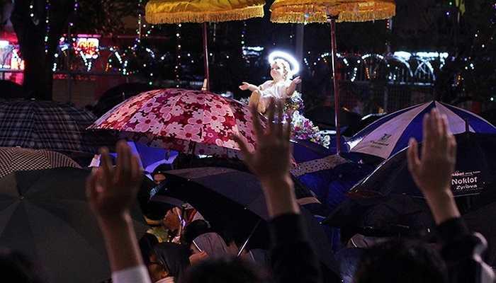 Đúng lúc rước tượng chúa Giê su Hài Đồng thì trời đổ mưa. Vừa dùng ô che mưa, người dân đứng hai bên vừa cố gắng với tay chào hài nhi