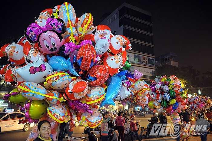 Những chùm bóng bay đầy sắc màu của chị Phạm Thị Thu (Nam Định), chị cho biết: 'Dịp Noel này tôi cũng tranh thủ nhập bơm nhiều bóng hơn và mong là đêm nay sẽ bán hết được số bóng này.'