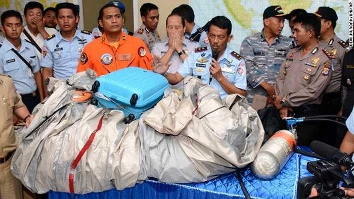Các thành viên Không quân Indonesia đưa ra những vật thể vớt được đầu tiên từ hiện trường vụ tai nạn trong đó có một vali của hành khách