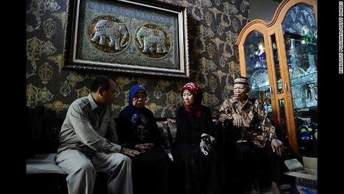 Widiya Sukati Putri, vợ của cơ trưởng (trùm khăn đỏ) và các thành viên gia đình đợi tin ở nhà riêng