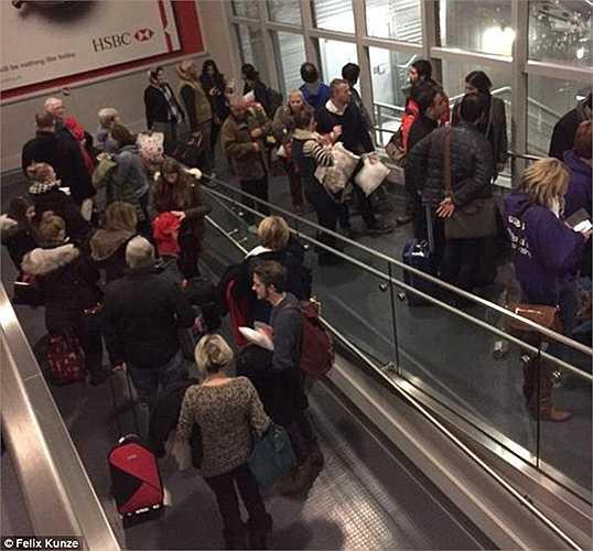 Các hành khách chờ đợi ở đường dẫn ra máy bay, trong khi tuyết ngoài trời rơi dày.