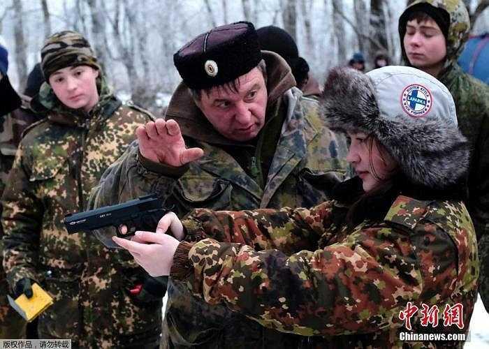 Một nữ sinh xinh xắn đang được dạy cách tập bắn súng ngắn.