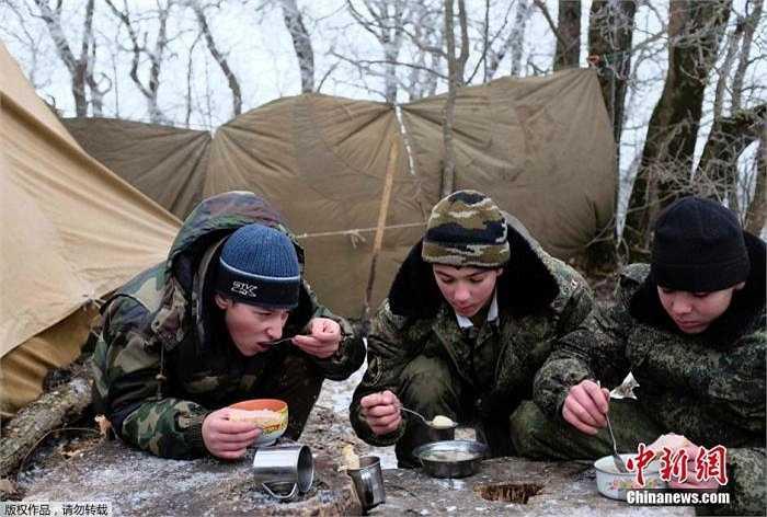 Ba nam sinh trong đồng phục lính đang ăn vội trong giờ nghỉ giữa trưa.