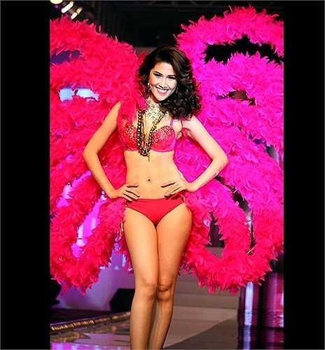 Chân dài Thu Hằng cũng khoe đường cong cơ thể với nội y và đôi cánh hồng, lấy ý tưởng từ các show diễn của Victoria's Secret.