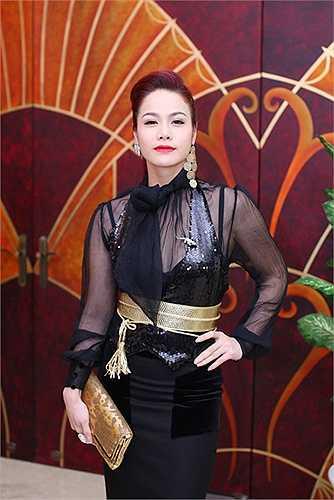 Nhật Kim Anh chọn đai lưng to bản và ví cầm tay trên cùng chất liệu và màu sắc của Gucci, tuy nhiên cô để hình ảnh của mình trở nên rối mắt với quá nhiều phụ kiện như: hoa tai, cài áo và váy đính kết nhiều chi tiết.