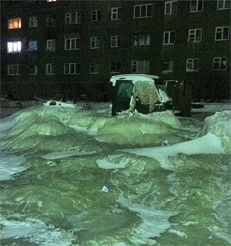 Xe tải chìm trong băng do nước tràn khỏi đường ống