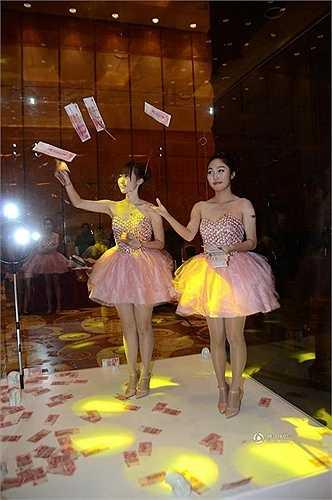 Hai người mẫu xinh đẹp tung những tờ tiền trong bể kính