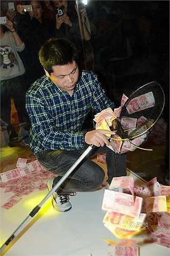 Một nam nhân viên dùng vợt để vớt tiền trong khoảng thời gian quy định của công ty.