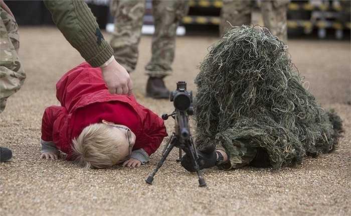 Cậu bé tò mò bên cạnh trang phục của một người lính Anh