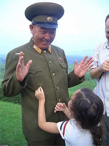 Một quan chức Triều Tiên, mặc quân phục đang tươi cười với bé gái.