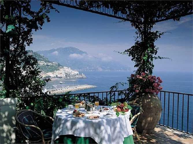 Một bữa sáng trong ánh nắng vàng trên tầng thượng với tầm nhìn ra biển lớn.