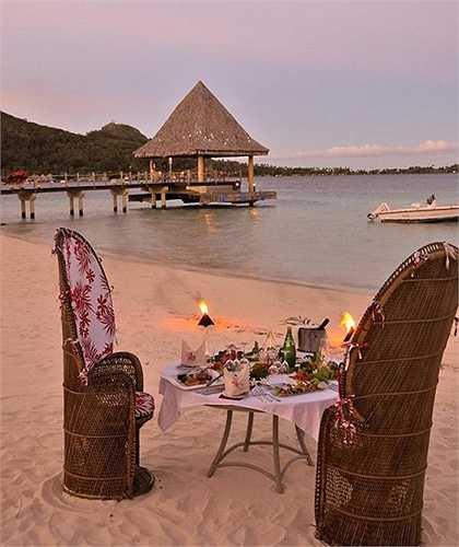 Một bữa tối trên cát biển với những ngọn nến lung linh.