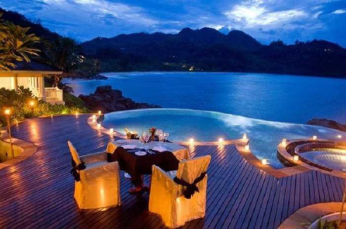 Bữa tối bên hồ bơi trong vắt có tầm nhìn ra biển rộng và những ngọn núi mờ ảo.