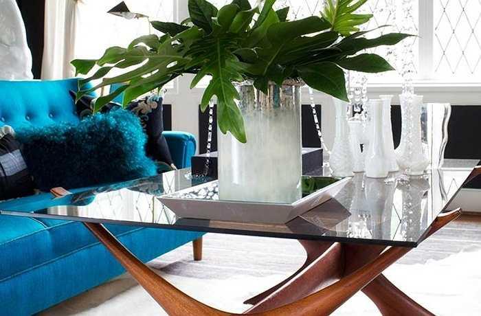 Một trong những cách tạo thu hút trong không gian là bàn cà phê hiện đại phong cách Bắc Âu với nền gỗ hồng sắc và mặt kính thủy tinh màu khói. Tính nghệ thuật trong điêu khắc và các tỉ lệ hoàn hảo của chiếc bàn đã làm cho nó phù hợp với không gian, nó cũng giúp phản chiếu nguồn ánh sáng dồi dào chiếu vào từ cửa sổ