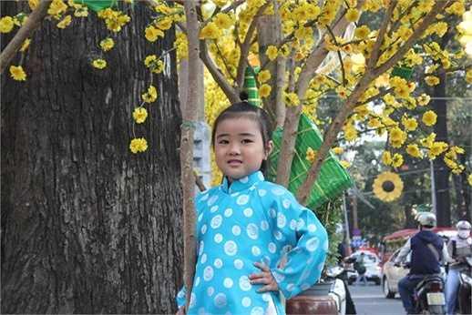 Một em nhỏ được phụ huynh dẫn đi chụp hình với chiếc áo dài xinh xắn (Ảnh: Phạm Nguyễn)