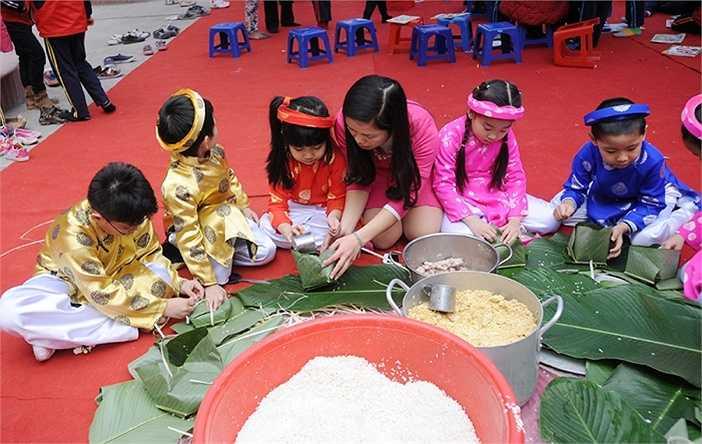 Các cô giáo sẽ hướng dẫn từng học sinh để các em có thể tự tay gói những chiếc bánh vuông vắn