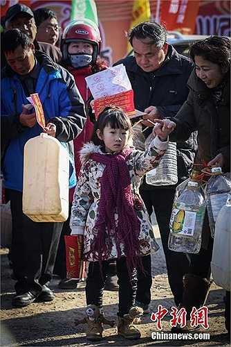 Mỗi người trên tay chuẩn bị can nhựa để lấy nước tương miễn phí