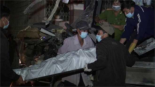 Nhà chức trách đưa thi thể nạn nhân ra ngoài. (Ảnh Zing)