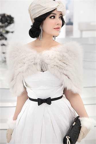 Kết hợp với chiếc khắn quấn cổ bằng lụa trắng, chiếc váy circle của thương hiệu Maticevski cùng với khắn lông găng tay da lộn của Elcom Fur và bông tai Crivelli