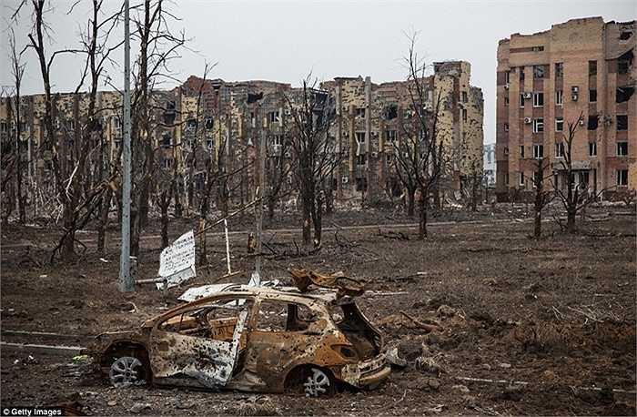Xác xe ô tô nằm chỏng chơ bên cạnh một khu nhà bị tàn phá tan tành ở Donetsk
