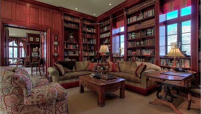 Phòng đọc sách được trang trí theo kiểu cổ với những giá sách cao ngất ngưởng chất đầy sách