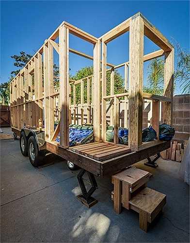 Khung ngôi nhà làm bằng gỗ, dưới chân có bánh xe để kéo đằng sau ô tô