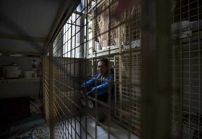 Một người đàn ông ngồi trong căn phòng nhỏ như chiếc lồng được thuê 1.500 nhân dân tệ/tháng