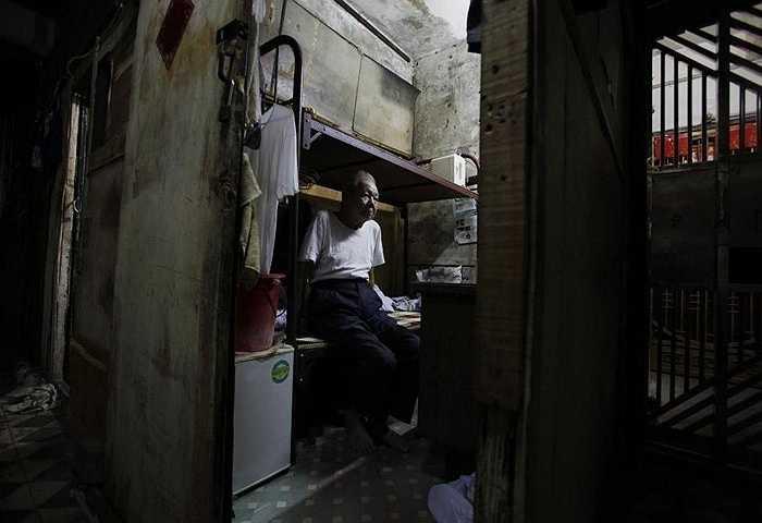 Ông Huang cùng vợ ngồi trên giường đặt chật cả căn phòng 4m2 được thuê hơn 1000 nhân dân tệ/tháng