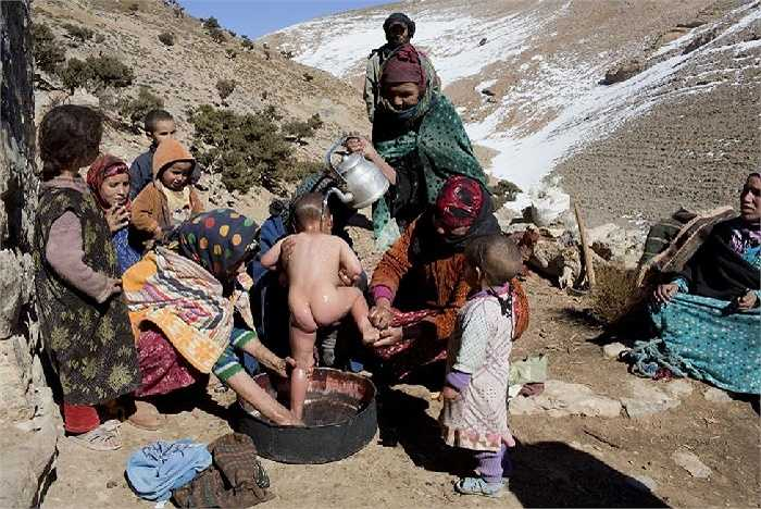 Phụ nữ Berber tắm cho một đứa trẻ trong làng Ait Sghir ở vùng núi Atlas, Morocco.