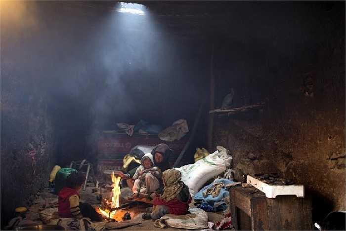 Bà mẹ sưởi ấm cho đứa con quanh đống lửa trong ngôi làng Tilmi, Morocco